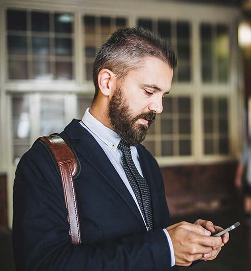Man looking at cell phone application to control home automation services