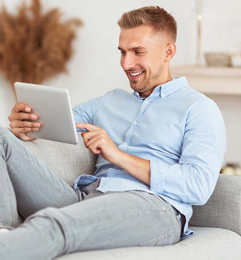 Guy sitting on couch using tablet app to control his home thermostat