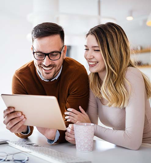 Couple in a kitchen using a tablet to set up connected home services